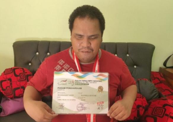 Foto Muhammad Ilham saat memperlihatkan piagam penghargaan