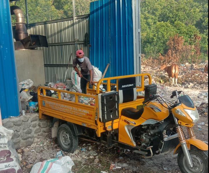 Petugas kebersihan Tanjung Bira menurunkan sampah dilokasi pengelolaan sampah. (foto: Devi)