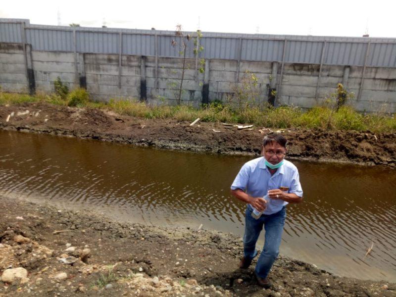 Kepala Teknisi PT Asindo, Pieter, saat mengambil sampel limbah tambak udang.